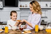 mosolygó nő pirítós lekvárral adva a konyha asztalnál aranyos lánya