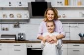 usmívající se žena všeobjímající roztomilý Dcera a při pohledu na fotoaparát v kuchyni