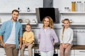 Fotografie lächelnden Eltern mit Tochter und Sohn Blick in die Kamera in Küche