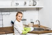 Fotografie roztomilá dívka v gumové rukavice mytí nádobí a při pohledu na fotoaparát v kuchyni