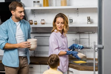 handsome man holding bowls and looking at pretty wife washing dishes and talking with son