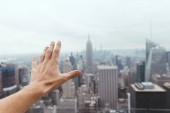 partial view of male hand and blurry new york city on background