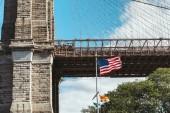Fotografie zblízka pohled na Brooklynský most a americká vlajka v new Yorku, usa