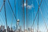 Fotografie Brooklynský most na modré oblohy a manhattan na pozadí, new york, usa