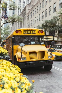 urban scene of yellow school bus and cars on street in new york, usa