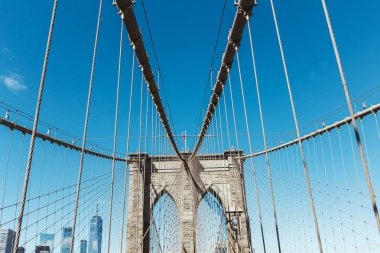 brooklyn bridge with american flag on clear blue sky and manhattan on background, new york, usa
