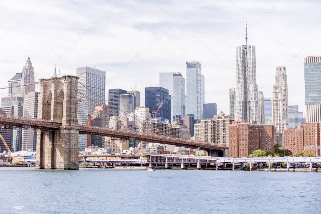 urban scene with brooklyn bridge and manhattan in new york, usa