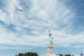 STATUE OF LIBERTY, NEW YORK, USA - OCTOBER 8, 2018: statue of liberty in new york against blue cloudy sky background, usa