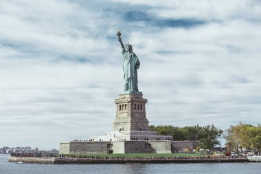 STATUE OF LIBERTY, NEW YORK, USA - OCTOBER 8, 2018: statue of liberty in new york against blue cloudy sky background, usa stock vector