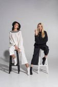 Fotografie beautiful multicultural women in fashionable black and white clothes sitting on chairs and looking at camera on white