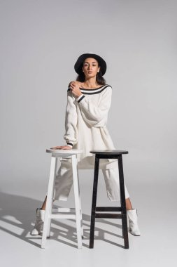 attractive african american girl in stylish white clothes and hat standing near black and white chairs on white