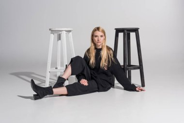 beautiful caucasian blonde woman in black clothes sitting near chairs and looking at camera on white