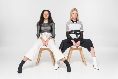 attractive multiethnic women in black and white clothes posing on chairs and looking at camera isolated on white