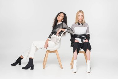 caucasian and african american women in black and white clothes sitting on chairs isolated on white