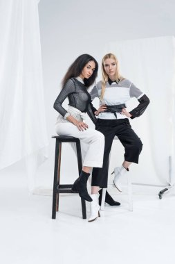 beautiful multiethnic women in black and white clothes sitting on chairs and looking at camera on white