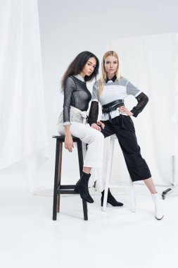 attractive multiethnic women in black and white clothes posing on chairs and looking at camera on white