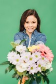 Fotografie selective focus of smiling child with flower bouquet looking at camera isolated on green