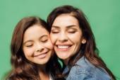Fotografie portrét happy matka a dcera se zavřenýma očima izolované na zelené