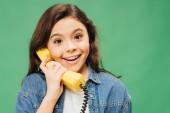 izgatott gyermek beszélni, vintage telefonon és látszó-on fényképezőgép zöld elszigetelt