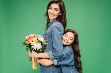 adorable daughter hugging smiling mother with flowers isolated on green