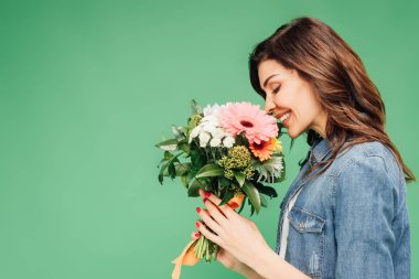 smiling woman holding and sniffing flower bouquet isolated on green