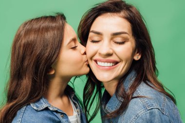adorable daughter kissing happy mother cheek isolated on green