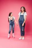 dcera v kolečkové brusle drželi se za ruce s mamince na růžovém pozadí