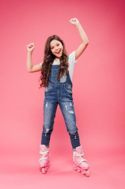 happy child in overalls and rollerblades cheering with arms in air on pink background