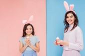 Fényképek gyönyörű nő és a gyerek nyuszi füle gazdaság cupcakes, és látszó-nél fényképezőgép kék és rózsaszín háttér