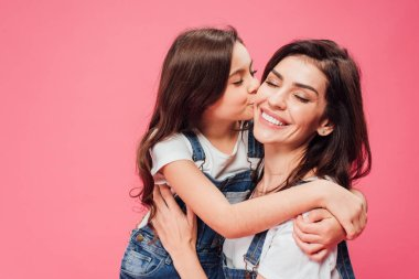 daughter kissing happy mother isolated on pink