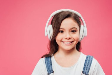 Smiling kid listening music in headphones isolated on pink stock vector