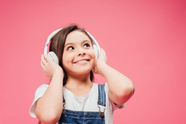 cheerful child listening music and touching headphones isolated on pink