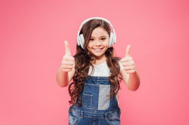 Smiling kid in headphones showing thumbs up isolated on pink stock vector