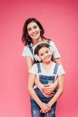 mother hugging daughter in headphones isolated on pink