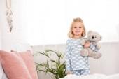 mosolygó gyermek állandó a hálószobában mackó pizsamában