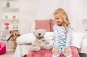 Fotografie s úsměvem roztomilé dítě sedí na posteli s Medvídek
