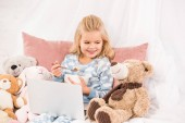 cute child with laptop eating cornflakes and looking at teddy bear in bed