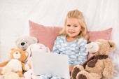 adorable child sitting in bed with soft toys and watching cartoons