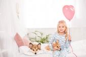 usmívající se dítě sedí na posteli s pembroke velšský corgi psy doma a drží srdce tvarovaný balón