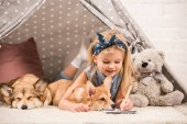 adorable child lying in wigwam with welsh corgi dogs and writing in notebook at home