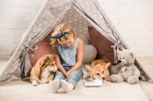Fotografie adorable child sitting with corgi dogs in wigwam at home