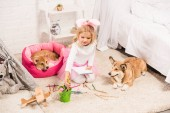 Fotografie child in bunny ears headband sitting with welsh corgi dogs at home and drawing with coloring pencils