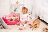 Fotografie adorable child in bunny ears headband sitting with welsh corgi dogs at home and reading book