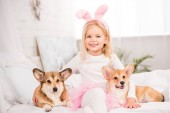 Photo cute child in bunny ears headband sitting with welsh corgi dogs on bed at home