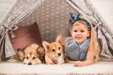cute child with welsh corgi dogs lying in wigwam and looking at camera