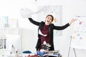 happy attractive businesswoman throwing up documents in office