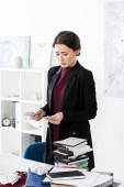 Fotografie sad attractive businesswoman counting euro banknotes in office