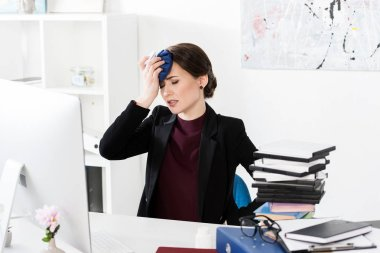 businesswoman having headache and touching head with ice pack in office