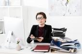 Fotografie attraktive Geschäftsfrau mit Brille, Klemmbrett haltend und im Büro wegschauend