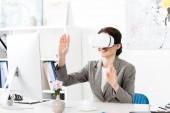 Fotografie Usměvavá podnikatelka pomocí soupravu pro virtuální realitu v kanceláři